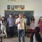 A classroom with people standing in front. Some students wearing school uniforms is sitting. A man is standing in front and talking. Blackboard in the background says IDIA.