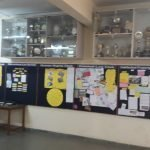 A corridor with trophies kept on top. Boards with various things pinned on them below it. Two people are standing in front of a table.