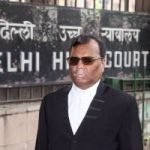 A man wearing a black suit and spectacles, standing and facing in front. Behind him is a board saying Delhi High Court.