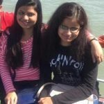 Two young women sitting on a boat. One of them has her arm around the other.