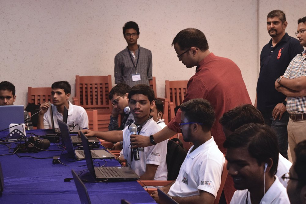 Some people are sitting around a table with laptops in front of them. One man is holding a mic for one of the students sitting. Some people are standing in the background.