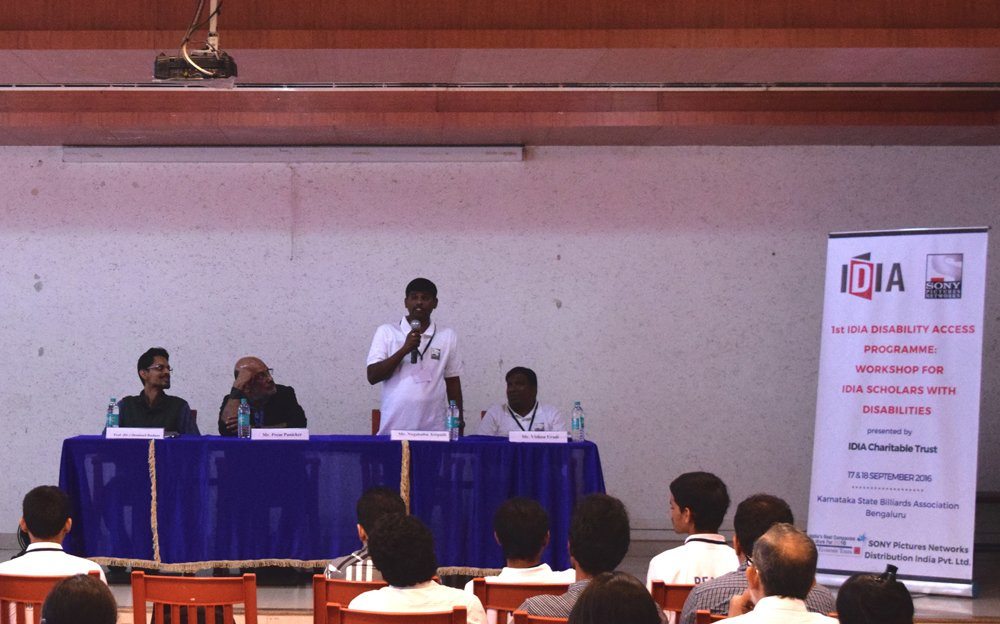 Audience. Four people on a stage. Three are sitting while one is standing and holding a mic. Next to them is a white standee with IDIA and Sony Pictures Networks logo on it. It says: 1st IDIA Disability Access Programme: Workshop for IDIA Scholars with Disabilities presented by IDIA Charitable Trust. 17&18 September 2016. Karnataka State Billiards Association Bengaluru