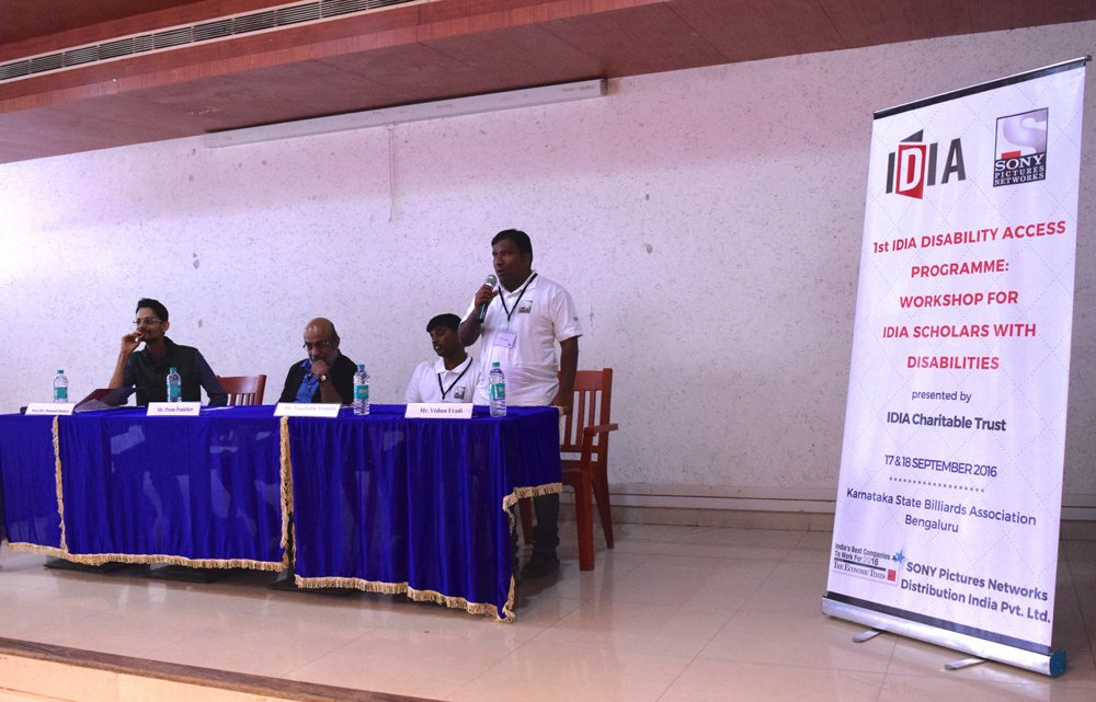 Four people on a stage. Three are sitting while one is standing and holding a mic. Next to them is a white standee with IDIA and Sony Pictures Networks logo on it. It says: 1st IDIA Disability Access Programme: Workshop for IDIA Scholars with Disabilities presented by IDIA Charitable Trust. 17&18 September 2016. Karnataka State Billiards Association Bengaluru