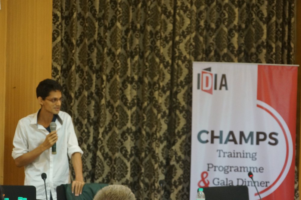 A man is holding a hand held mic and talking. There is a standee saying IDIA CHAMPS Training Programme next to him.