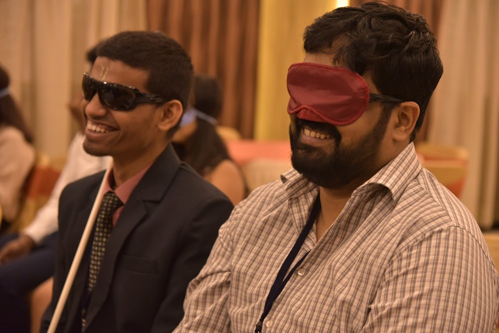 Two people are sitting and smiling. One of them is wearing black spectacles. The other person is wearing a red blind fold.