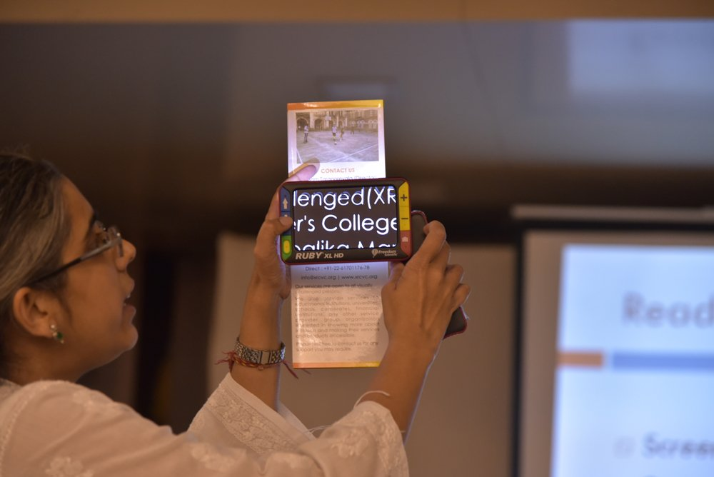 A woman is standing and showing a device that is magnifying the text on a paper clipping.