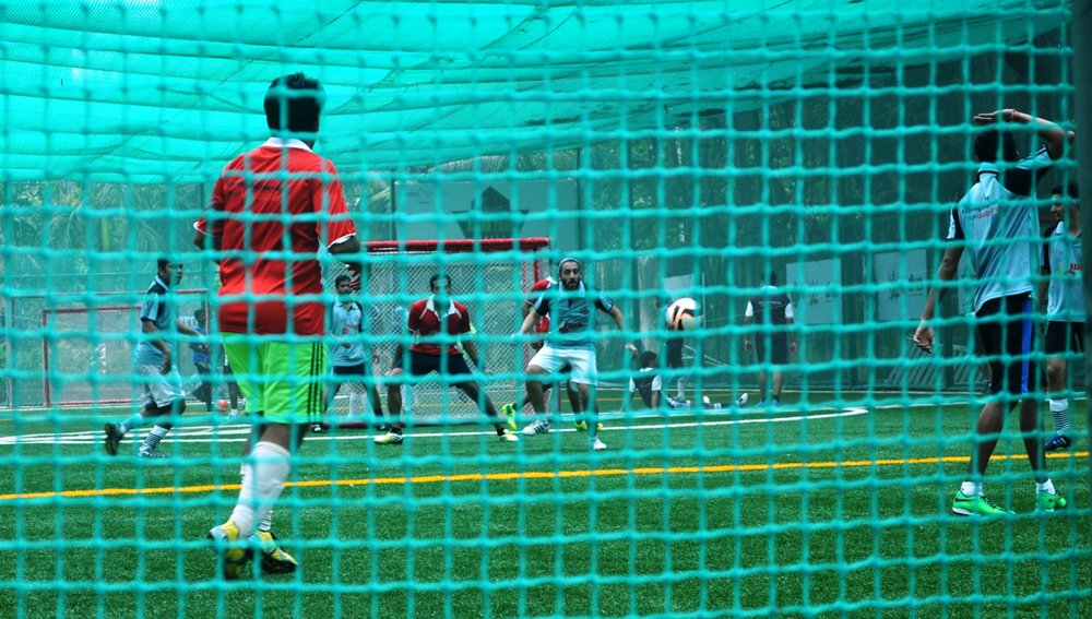 Two football teams are playing the sport vigorously. The white jersey team is ready to kick a goal and the red jersey team member is at goalpost ready to defend.