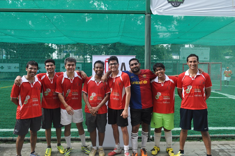 A group of people in sports jerseys standing and posing for a photograph. They are smiling towards the camera.