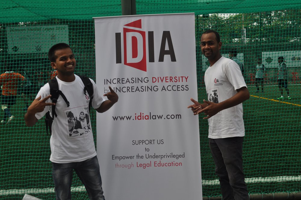 Two people are standing on either side of a white board with IDIA logo. It has Increasing Diversity by Increasing Access written on it. There is a net and football field in the background.