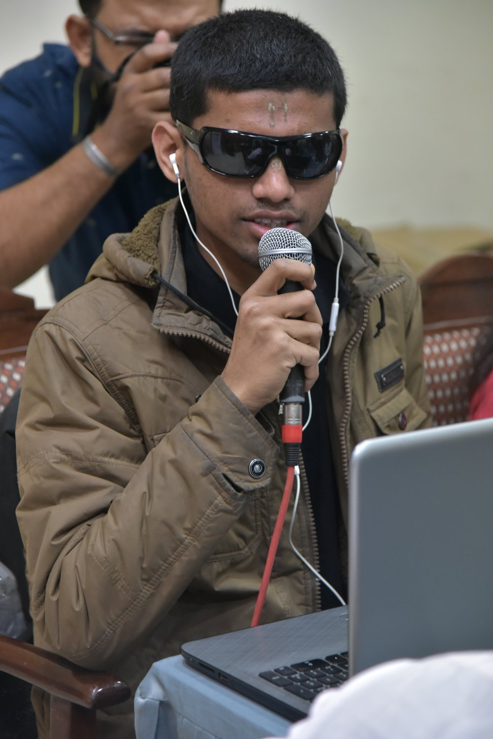 A young man is holding a hand held mic and talking. He is wearing black spectacles. There is a laptop in front of him. Someone behind him is clicking a photograph with a camera.