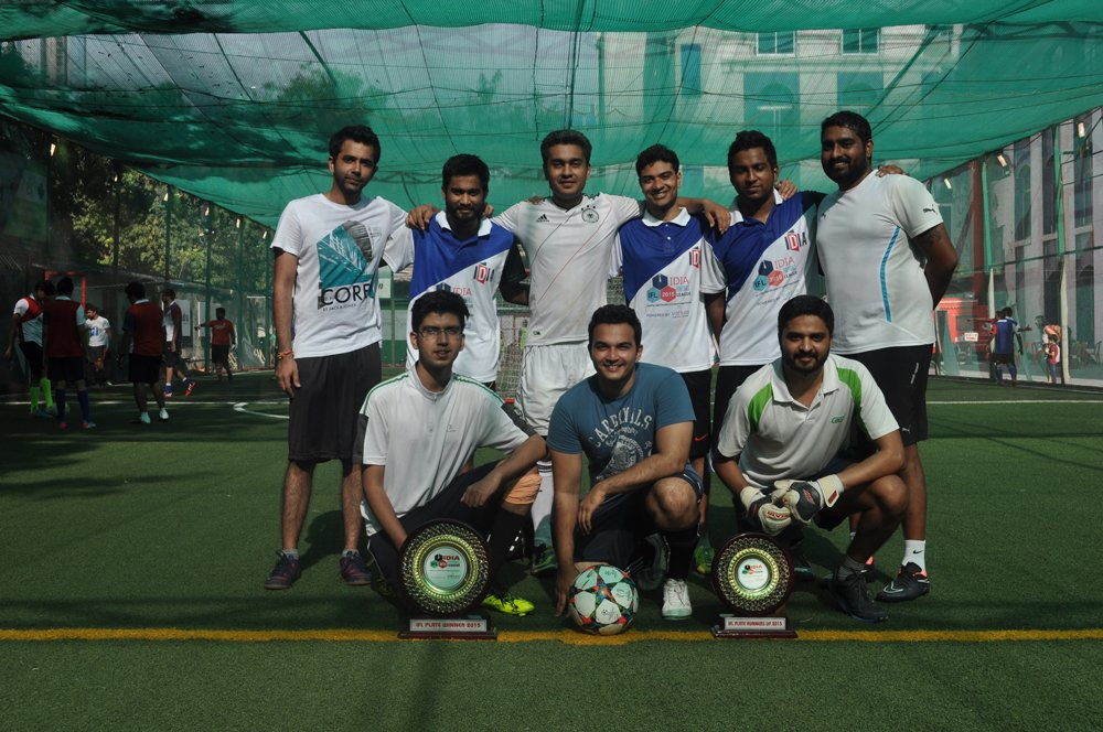A group of people in sports jerseys posing with some trophies. Some of them are sitting while others are standing.
