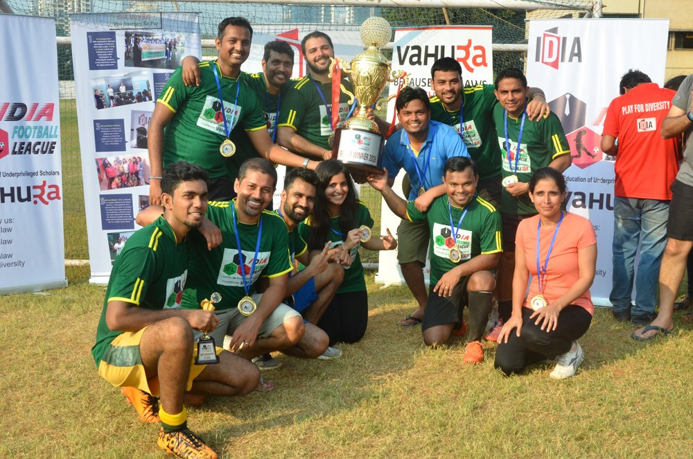 A group of people in green jerseys and some other people are posing for a picture on a field. Some of them are holding a trophy.