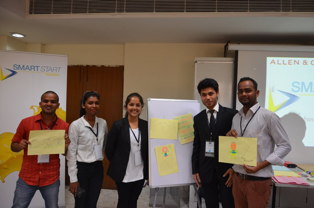 A group of people are standing and smiling towards the camera. Some of them are holding pieces of paper. There is a white board in middle of them with some papers on it.