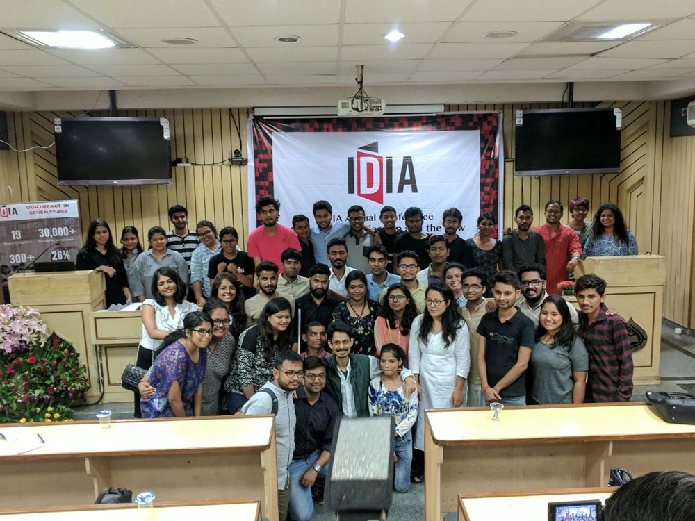 A group photo is a room with a banner with IDIA logo in the background.