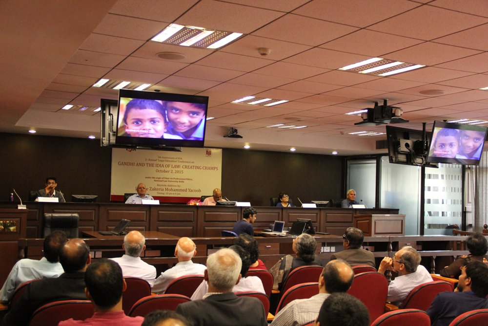A conference room with a video playing on screens. Some people are sitting on a stage. The chairs are filled with audience.