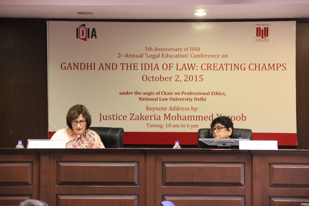 "Two women are sitting on chairs on a stage. One of them appears to be talking. In the bakcground there is a board about the conference with its name: ""Gandhi and the IDIA of Law: Creating CHAMPS"""