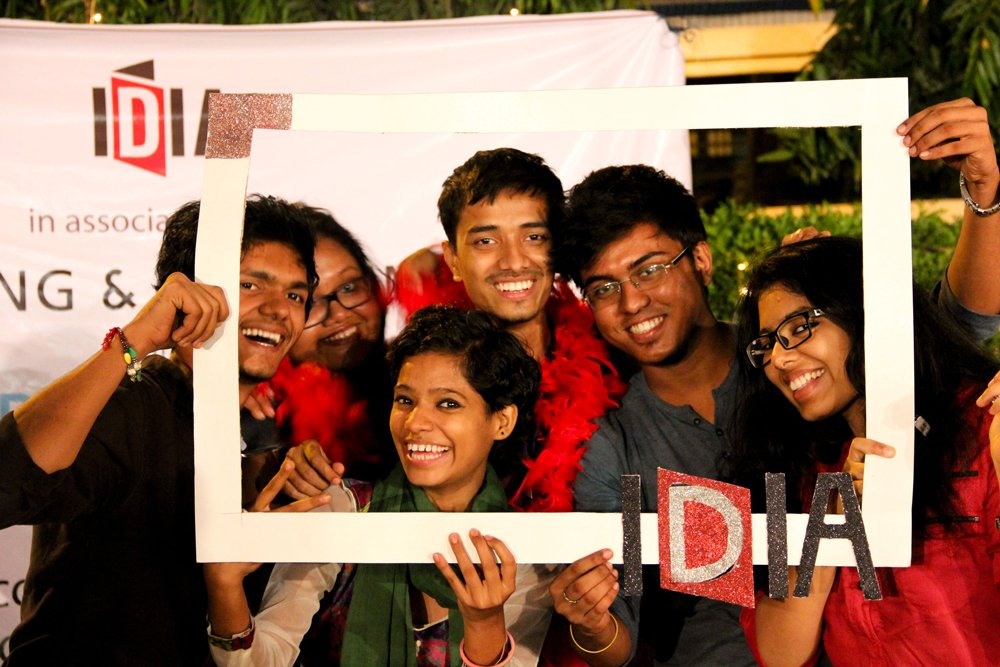 A group of people looking towards the camera and smiling. They are holding up a paper-cut-out in shape of a frame with IDIA Logo at bottom left of the frame