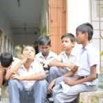 A group of boys sitting on stairs and in a corridor.