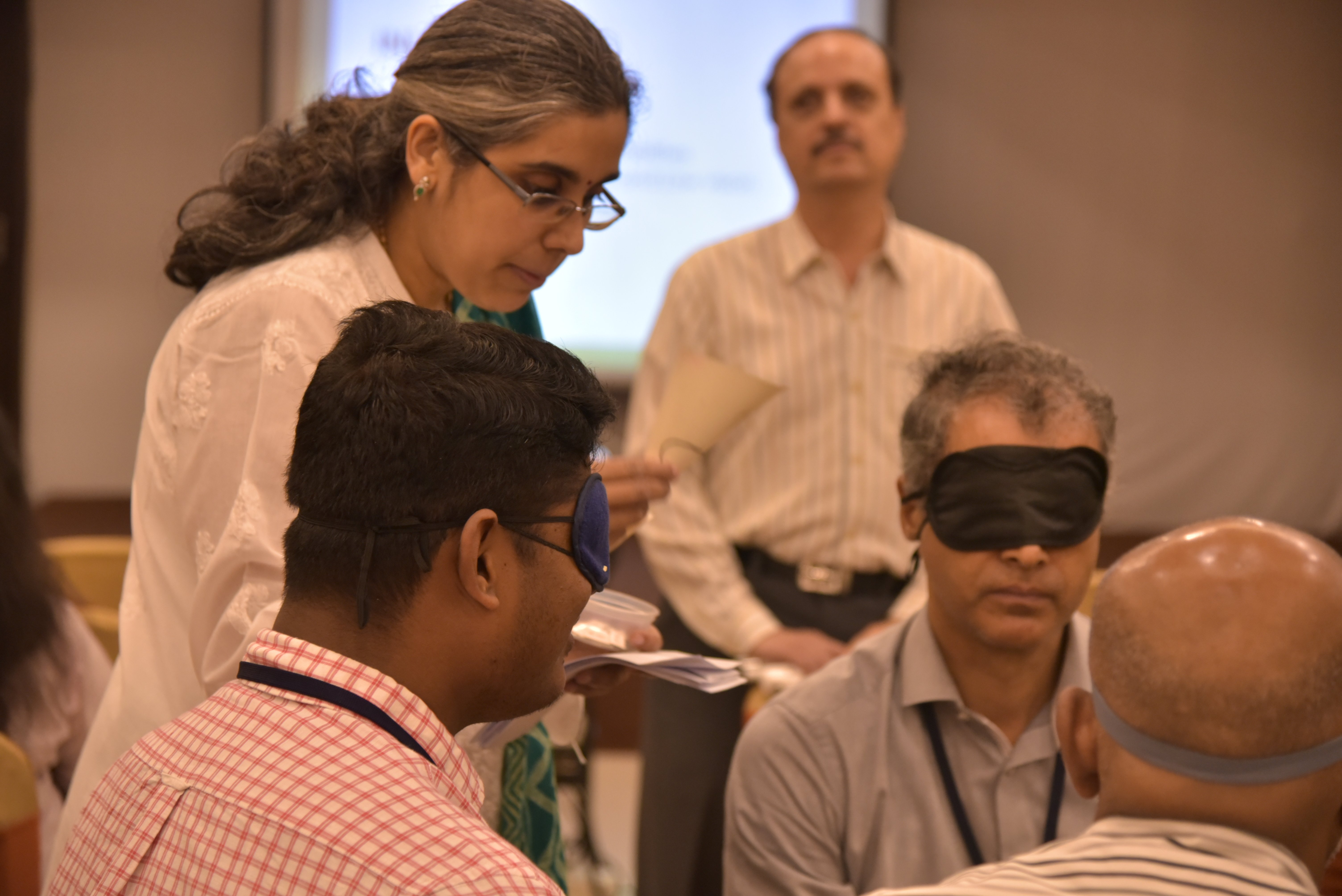 Some men are sitting and wearing eye masks. A woman is standing and holding a piece of paper. One more man is visible in the background.