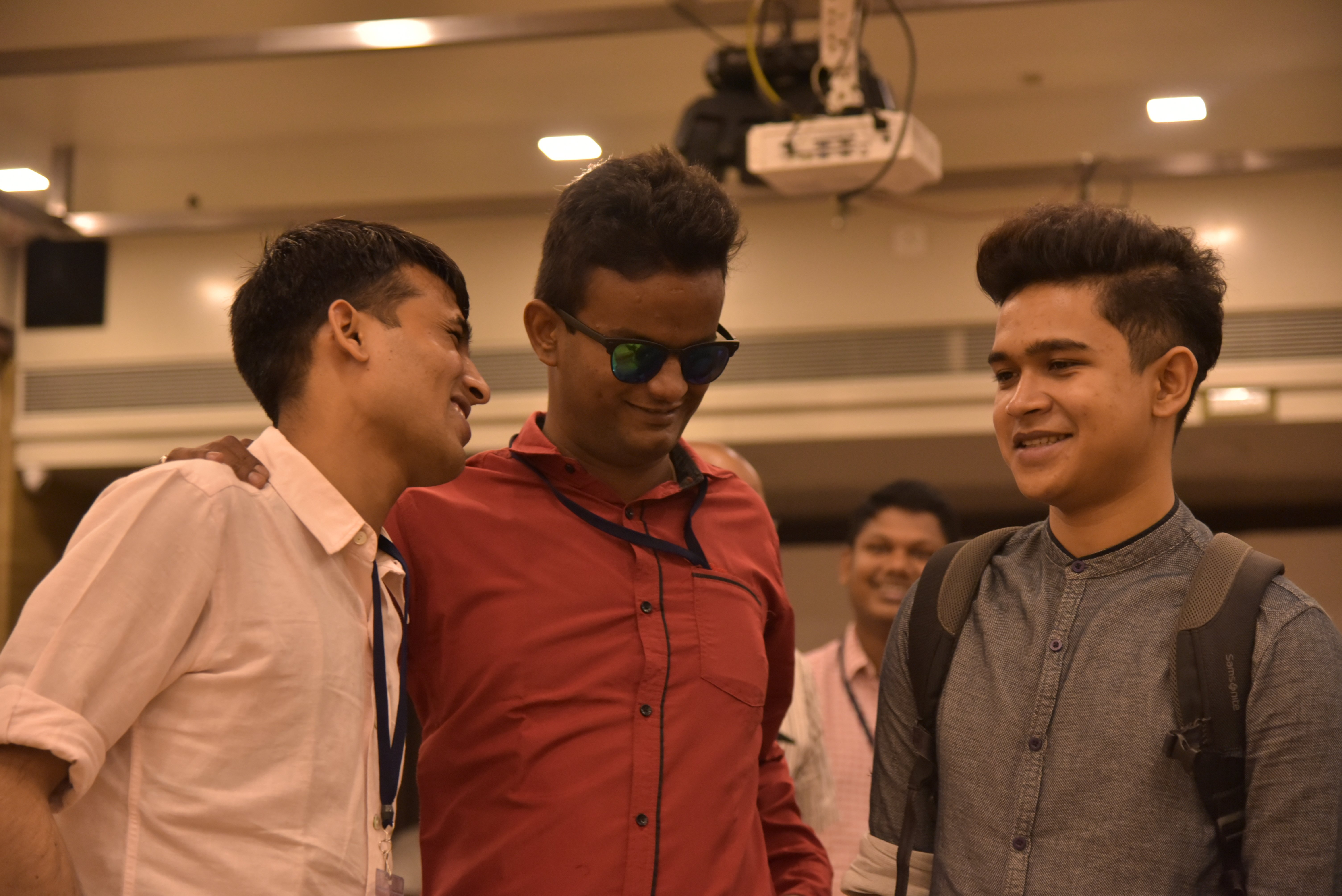 Three young men are standing and smiling. One of them is wearing black spectacles. One more person is visible in the background.
