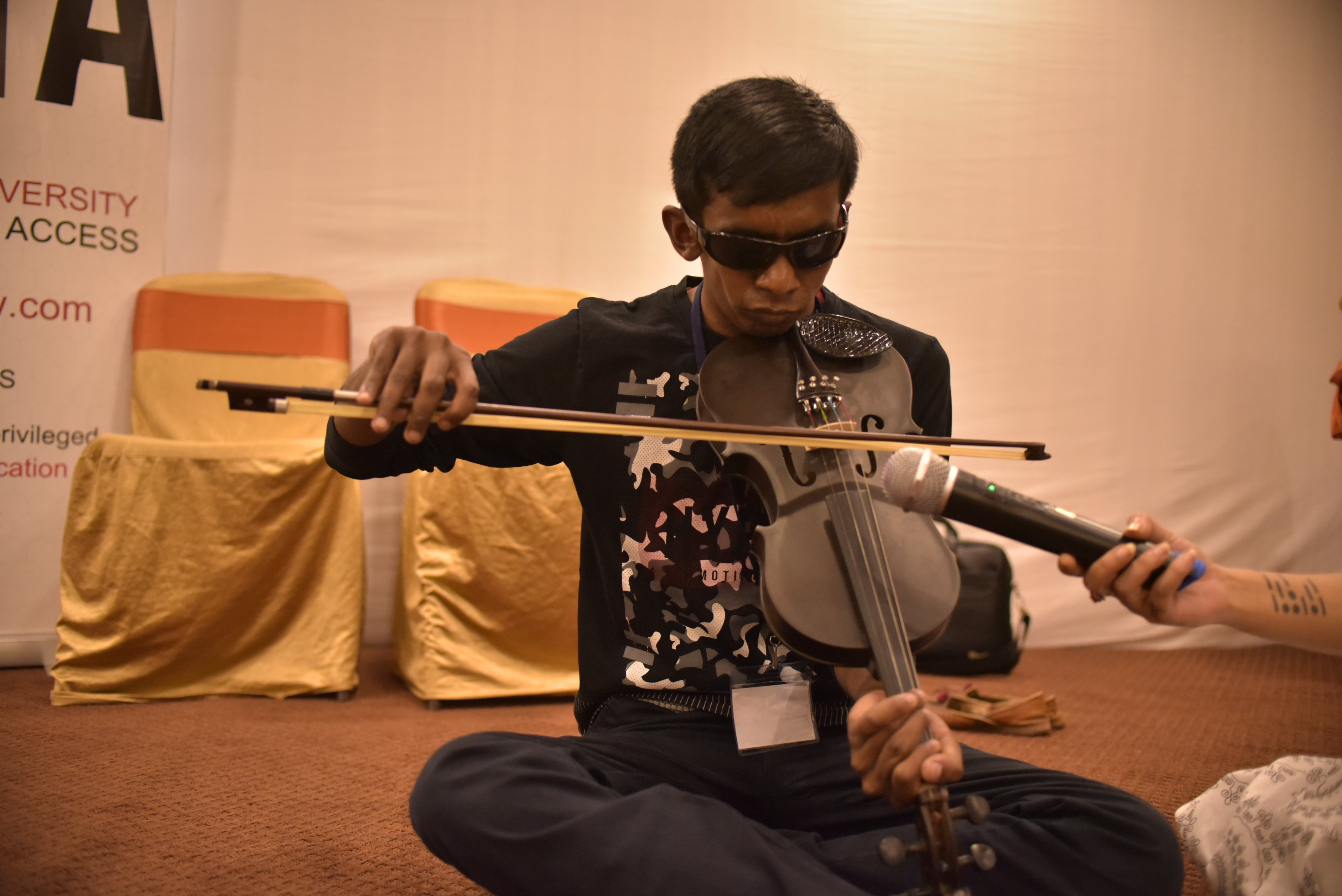 A young man sitting and playing a violin. He is wearing black glasses. Someone is holding a mic in front of him.