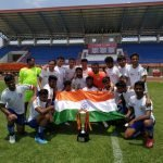 Team in jerseys in a group holding India's flag with a trophy kept in front of them.