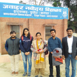A group of 5 people are standing in front of a board saying 'Jawahar Navodaya Vidyalaya' in Hindi.