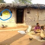 "Photograph of a house with 'Mera Parivar Garib Hai"" painted on it. Two children are sitting in front of the house."