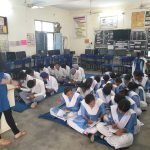 A girl is wearing blue kurta and standing in front of the classroom. She is addressing students wearing white and blue school uniforms and sitting on the ground.