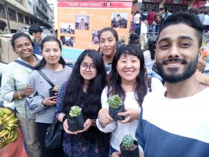 A selfie of around 6 people. Some of them are holding saplings/plants.