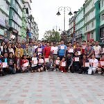 Group picture on a street with building in the background. Some of the people are holding certificates.