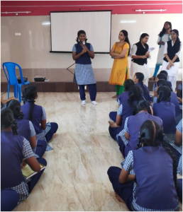 Students in school uniform are sitting on the floor in rows. One student is standing and speaking into a mic. Some other students and other people are also standing near her.