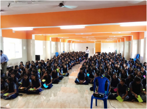 A large group of students in school uniform are sitting on the floor in rows.