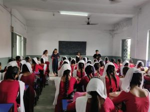 A group of girls in school uniforms are sitting on chairs. Some people are standing in front of them. One of them is talking. There is a blackboard in the background.