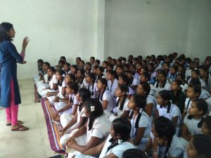 A young woman is standing and talking to a group of girls in school uniforms who are sitting on carpets on the floor.