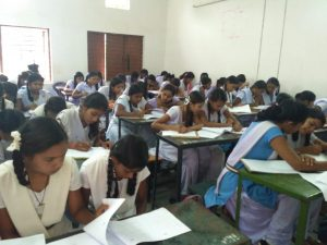 A group of girls in school uniforms are sitting on benches with papers in front of them on tables. Some of them writing and some of them are reading.