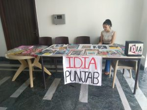 A table stacked with posters and phulkaris. A poster saying IDIA Punjab is pasted on the table. A girl is sitting on the other side of the table.
