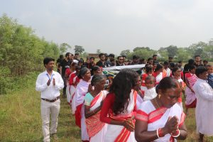 Women in red and white saris are walking. Behind them, some young men and women are walking. Some of them are holding a banner. They are wearing black T-shirts. A young man wearing white shirt and pant is walking on the left.