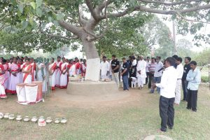 There is a large tree in the middle. On the left hand side of the tree, some women in red and white saris are standing. Some drums and water pots are kept in front of them. On the right hand side of the tree, some men are standing.
