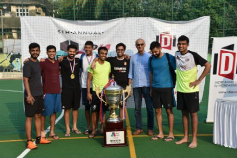 A group picture of men. There is a huge trophy kept in front of them. There is a white banner in the background.