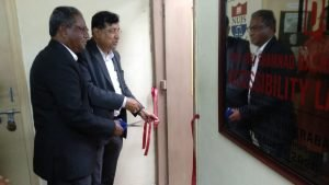 A cut ribbon across the door of a room. One man is holding a side of the ribbon. Another man is holding scissors.