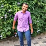 A young man wearing purple shirt and blue jeans is standing and smiling towards the camera. There is a shrub with leaves and flowers in the background.