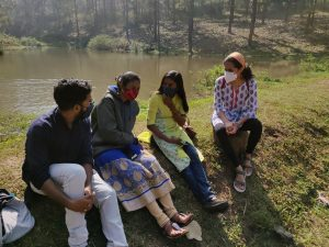 Four people sitting with masks on