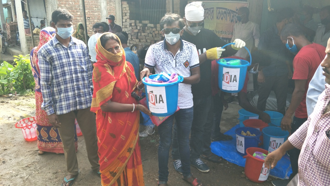 Photograph of a person handing over buckets contraining provisions to a woman. There are other people standing in the background. Buckets with provisions are kept below.