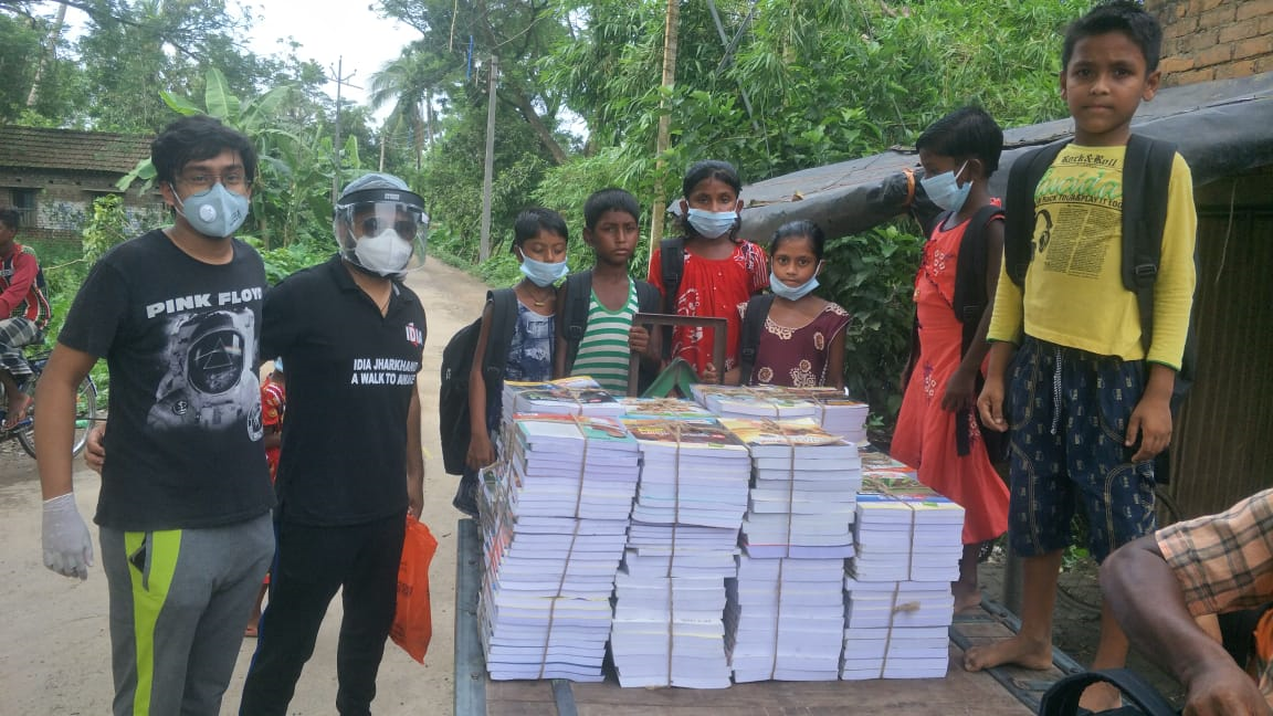 A pile of books kept in front. Some kids and two adults standing behind them.