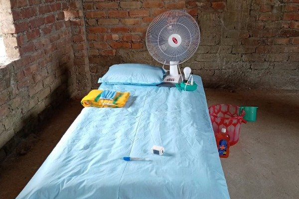 Photograph of a bed with fan, pillow and other things kept on it. There is a blue bedsheet on it and some other provisions are kept on it.