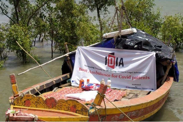 """Photograph of a boat with a white banner that has IDIA logo and """"Boat Ambulance for Covid patients"""" written on it. There are some provisions kept on the boat."""